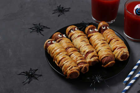 Spooky sausage mummies and tomato juice for Halloween party on dark plate. Funny food idea for kids. Space for text.