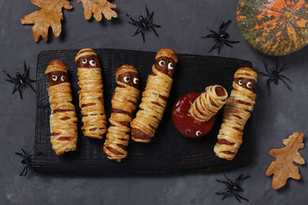 Spooky sausage mummies and tomato sauce for Halloween party on dark wooden board. Top view. Flat lay.