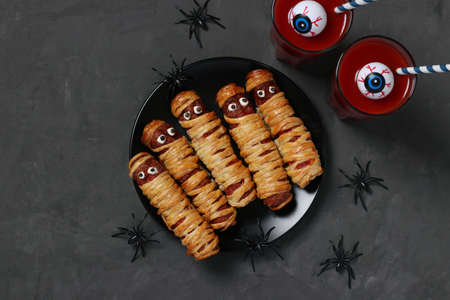 Spooky sausage mummies and tomato juice for Halloween party on dark plate, Top view. Flat lay. Horizontal format.