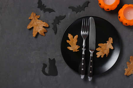 Halloween table setting is decorated with pumpkin shaped candles, bats and horror party decor on black table. Space for text.