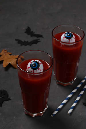 Eyes in glass with tomato cocktail on dark table for Autumn Holiday Halloween. Vertical format. Reklamní fotografie
