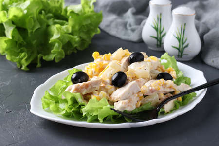 Salad with pineapple, baked chicken, corn and black olives on white plate on dark background Reklamní fotografie