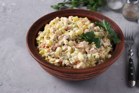 Traditional Russian salad Olivier in bowl on gray background, horizontal format. Closeup