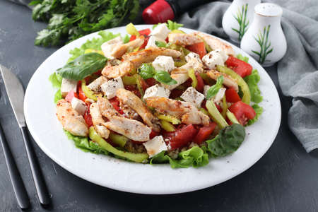 Salad with bulgur, baked chicken, bell pepper, basil and feta on white plate on dark background, Closeup. Horizontal format