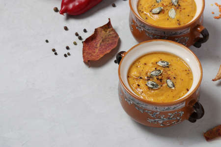 Vegetarian autumn creamy pumpkin soup with red lentils on gray background, copy space, close up Reklamní fotografie