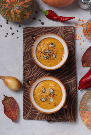 Vegetarian autumn pumpkin soup puree with red lentils in two bowls on gray background. Top view. Reklamní fotografie