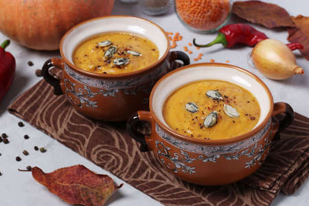Vegetarian autumn pumpkin soup puree with red lentils in two bowls on gray background. Closeup Reklamní fotografie