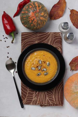 Vegetarian autumn creamy pumpkin soup with red lentils on gray background. Top view.