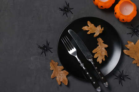 Halloween table setting is decorated with pumpkin shaped candles, spiders and horror party decor on black table. Space for text.