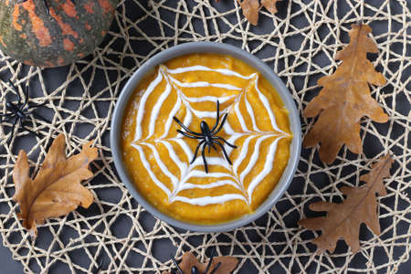 Halloween pumpkin soup with creamy spider web in gray bowl and spiders on the table. Top view