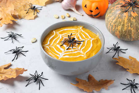 Halloween pumpkin soup with creamy spider web in gray bowl and spiders on the table. Closeup Reklamní fotografie