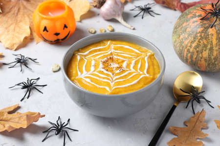 Halloween pumpkin soup with creamy spider web in gray bowl and spiders on the table.