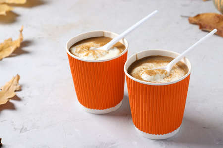 Paper cups with tasty pumpkin latte and spice on gray table. Closeup. Horizontal format Reklamní fotografie
