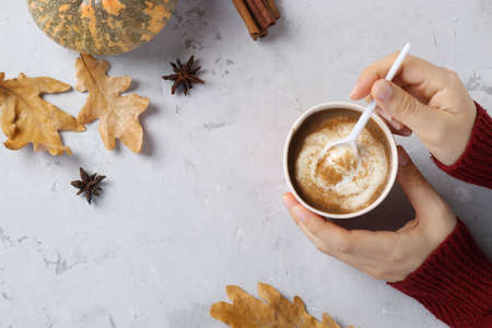 Paper cup with delicious pumpkin latte with spices in female hands on a gray table. Top view. With place for text. Reklamní fotografie