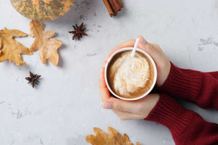 Paper cup with delicious pumpkin latte with spices in female hands on a gray table. View from above. With place for text.