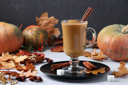Pumpkin latte with spices in glass on dark background with pumpkins and autumn leaves, close-up