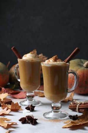Two glass cups pumpkin latte with spices on dark background with pumpkins and autumn leaves, close-up. Vertical format