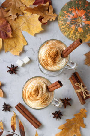 Two glass cups pumpkin latte with spices on gray background with pumpkins and autumn leaves. Top view. Reklamní fotografie