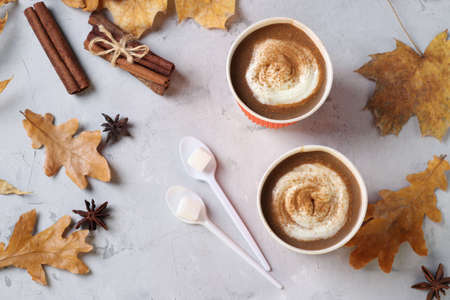 Two paper cups with tasty pumpkin latte and spice on gray table with autumn leaves. Top view.