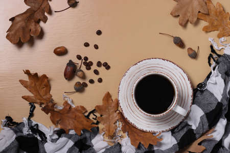 Acorn coffee with fall oak leaves and checkered scarf on beige background. Coffee substitute without caffeine. Top view. Space for text. Reklamní fotografie