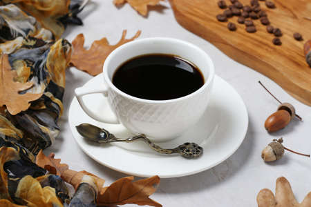 Acorn coffee with fall oak leaves on gray background. Coffee substitute without caffeine. Closeup. Reklamní fotografie