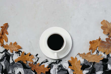 Cup of coffee and fall oak leaves with checkered scarf on gray background.Top view. Flat lay. Reklamní fotografie