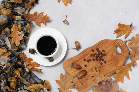 Acorn coffee with fall oak leaves on gray background. Coffee substitute without caffeine. Top view