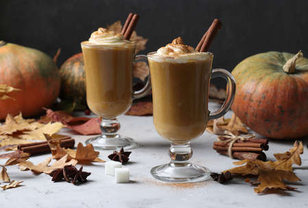 Two glass cups pumpkin latte with spices on grey background with pumpkins and autumn leaves, close-up.