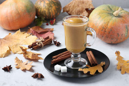 Pumpkin latte with spices in a glass glass on gray background with pumpkins and autumn leaves. Horizontal format.