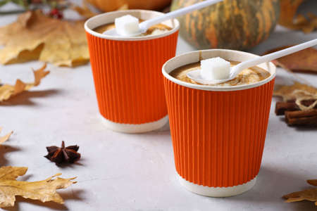 Paper cups with tasty pumpkin latte and spice on gray table. Closeup.