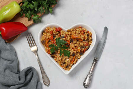Homemade pasta ptitim with vegetables on heart-shaped plate on gray table. Top view. Horizontal format. Reklamní fotografie