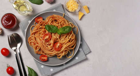 Spaghetti with tomato sauce and cherry tomatoes with basil on gray plate, Top view, Space for text