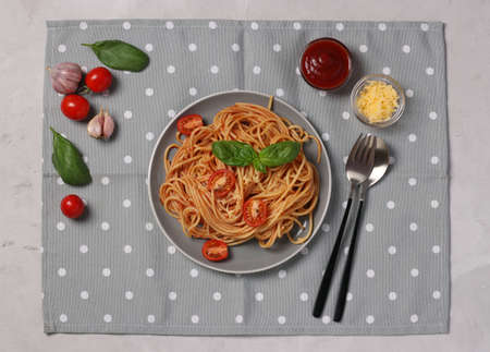 Spaghetti in tomato sauce and cherry tomatoes with basil on plate and gray napkin. View from above.