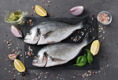 Fresh ready to cook raw fish dorado with ingredients and seasonings like basil, lemon, salt, pepper, red onion and olive oil on dark background, top view