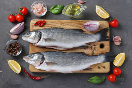 Raw fish seabass with ingredients and seasonings like basil, lemon, salt, pepper, cherry tomatoes and garlic on wooden board on dark background. View from above