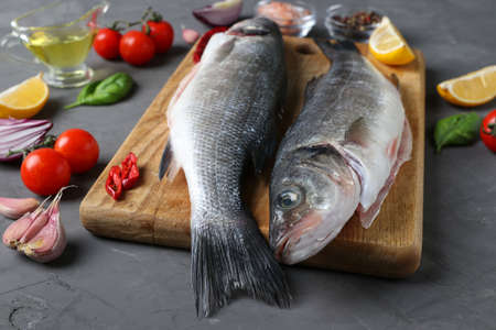 Two raw fish seabass with ingredients and seasonings like basil, lemon, salt, pepper, cherry tomatoes and garlic on wooden board on dark background. Closeup. Horizontal format Reklamní fotografie