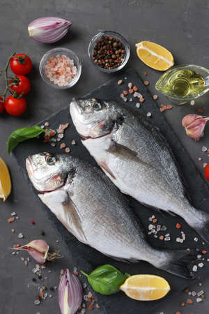 Two raw fish dorado with ingredients and seasonings like basil, lemon, salt, pepper, cherry tomatoes and olive oil on dark background, top view Reklamní fotografie