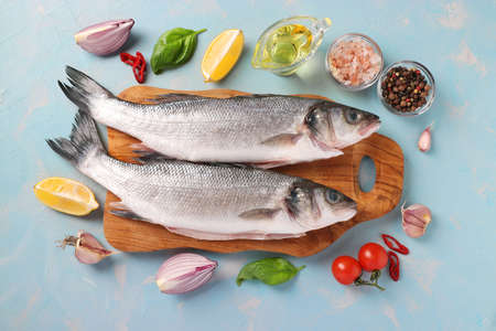 Raw fish seabass with ingredients and seasonings like basil, lemon, salt, pepper, cherry tomatoes and garlic on wooden board on light blue background. View from above