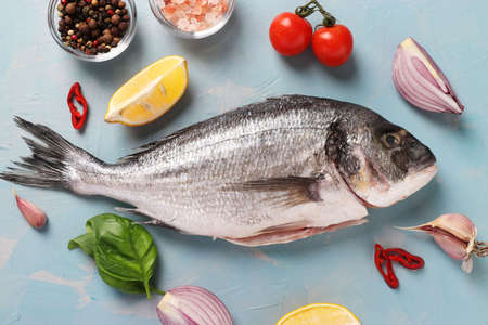 Fresh ready to cook raw fish dorado with ingredients and seasonings like basil, lemon, salt, pepper, cherry tomatoes and garlic on light blue background, top view