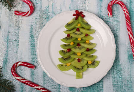 Christmas tree made from kiwi, corn and pomegranate, creative idea for Christmas and New Year festive dishes, fruit snack for children. Top view Reklamní fotografie