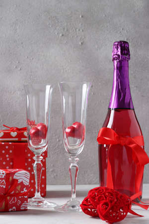 Happy Valentines Day concept. Romantic dinner with a bottle of pink champagne, glasses, heart shaped sweets and gifts on a light gray background. Vertical format