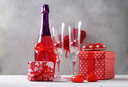 Happy Valentines Day Still Life. Romantic dinner with a bottle of pink champagne, glasses, heart shaped sweets and gifts on a light gray background.