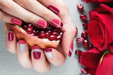 Skin care of a beauty female hands with grey, pink and red asymmetry nail art manicure. And pockmarked grey background with red roses and pomegranats seeds Stock Photo