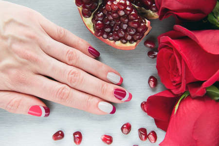 pomegranat: Skin care of a beauty female hand with grey, pink and red asymmetry nail art manicure. And pockmarked grey background with red roses and sliced pomegranat
