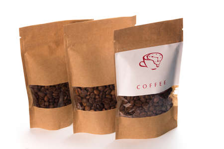brown coffee grains into the three paper packages on the white, isolated Foto de archivo