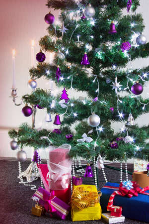decorated Christmas tree with gifts around and with the lit white candlestick Stock Photo