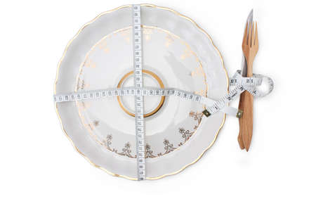 a plate, a fork and a knife, entwined by measuring tape on a white background  isolated Stock Photo