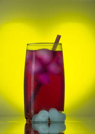 Two ice in the form of heart in the foreground and a glass of cold red cocktail with ice and straw on a yellow background in the shape of a heart Stock Photo