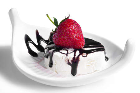 crankle: ripe red strawberry on a white ice cream drizzled with chocolate sauce leaving a zigzag trail on a white plate, isolated on white