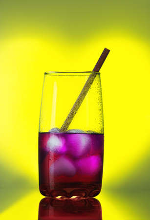 Glass of cold red cocktail with ice and straw on a yellow background in the shape of a heart Stock Photo